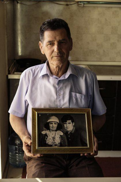 """Vase Jaku e sua moglie Vitore. Vase Jaku è nato nel 1950, nel mezzo della bufera comunista. A 17 anni lavorava la terra in una cooperativa nella sua zona.  Quel periodo per una famiglia cattolica  """"Era come avere un morto in casa, triste, tutto ciò che è religioso doveva avvenire di nascosto"""".  Due anni dopo iniziò a svolge il suo servizio d'obbligo di 2 anni nell'esercito e, a ventuno anni, conobbe Mikel Beltoja, un sacerdote perseguitato dal Regime. Con Mikel si instaura un rapporto di amicizia, spesso andavano in bici insieme, in zone isolate, per poter parlare liberamente all'insaputa degli ufficiali del regime. Nel 1973, però, Don Mikel fu arrestato con l'accusa di svolgere funzioni religiose, fu torturato e quando venne fissato il giorno del giudizio Vase cercò in tutti i modi di entrare. A quel punto, ascoltò con le sue orecchie il sacerdote rifiutare di rinnegare la sua fede per avere la vita salva e così venne condannato a morte. Alla fine del processo lo seguì fuori. Quando lo portarono via gli agenti, Mikel era uno scheletro, non riusciva nemmeno a salire in macchina, da lì in poi non lo vide più.  All'età di 23 anni sposò Vitore, classe 1954, che aveva 19 anni. Sono gli anni successivi alla dichiarazione di stato laico e l'abolizione di tutto ciò che fosse religioso. Così si sposano in segreto su una montagna.  La Famiglia Jaku è molto unita e religiosa, per questo celebravano le funzioni religiose di nascosto, con sacerdoti che arrivavano a casa vestiti come contadini o imbianchini per non farsi riconoscere.  Dopo il matrimonio Vase era a capo di quella piccola cooperativa che lavorava la terra, per un pezzo di pane al giorno, questo per la sua bravura nel fare i conti. Nel frattempo vendeva tabacco di nascosto, fino alla svolta per il popolo Albanese, il 13 Novembre 1990, quando si riprende la libertà.  Oggi Vase continua a vendere Tabacco e ha una famiglia numerosa con 8 figli. Tra loro due selle sue figlie e due sue nipoti sono suore.  Ha dei nipotin"""