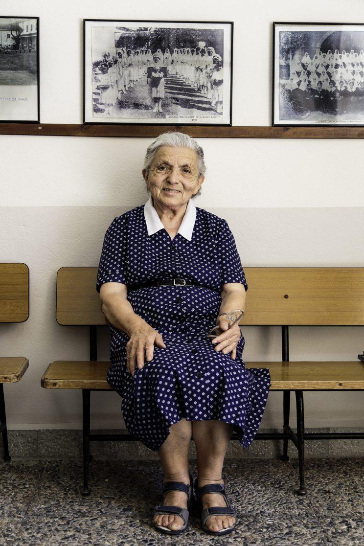 Suor Roza kraja - Convento Suore Stimmatine - Scutari - Albania. Suor Roza Kraja nasce il 13 Marzo del 1931 a Scutari. A 10 anni entra nella scuola delle suore Stimmatine di Scutari. Da piccola conosce Marie Tuci, che la aiuta spesso per la sua giovane età. Il 10 Marzo del 1946, prima di compiere il suo 15° compleanno il 13, il convento viene chiuso e vengono cacciate, compresa Marie che si trasferisce ad insegnare altrove. Suor Roza torna dai genitori, ha due fratelli minori e due sorelle maggiori. Per 10 anni cerca di aiutare la sua famiglia ricamando, dopo di che si reca alla chiesa francescana alle 6 per ascoltare la messa. Nel frattempo Marie viene arrestata e portata nella prigione di Scutari, dove viene torturata e si ammala di tubercolosi. Si narra che la si mise in un sacco con un gatto e venne bastonata per sfigurarla. Suor Roza e altre amiche di scuola vanno in ospedale e quasi non la riconoscono, è malata e magrissima, dopo di che non la vedranno più. All'età di 25 anni si scrive alla scuola per infermieri ma, dopo appena 2 giorni viene cacciata perché suo zio era stato in prigione per ragioni politiche. Il fratello della moglie di suo zio è un medico e la aiuta a riprendere gli studi. E' una studentessa brillante e alla fine degli studi, dopo qualche anno passato in chirurgia, gli viene assegnata una zona di Scutari dove fa l'infermiera per la gente del posto. Gira in bici e fa vaccini, pesa e ha cura dei bambini. Un giorno salva la vita ad un bambino prematuro portandolo in ospedale. Per 25 anni collabora con un pediatra e, all'età di 55 anni, va in pensione e torna a casa dove c'è ancora suo padre. A 60 finisce il comunismo e a 61 anni la proclamano suora dell'ordine delle Stimmatine senza noviziato. Dal 91 per 11 anni  collabora come cuoca nel convento fino ad avere problemi di salute come la broncopolmonite. Attualmente vive nel convento delle Suore Stimmatine a Scutari.