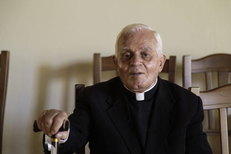 """Don Gjergj Simoni nel Seminario di Scutari - Albania. Gjergj Simoni nasce l'8 Dicembre nel 1933, è il fratello di Zef  Simoni, autore del libro """"Luci nella Tenebra"""", diventato vescovo dopo la caduta del regime. Per vivere lavora come operaio all'idrocentrale di Vau Dejes. Tra il 1946 e il 1950 la polizia occupa l'arcivescovado, Gjergj e suo fratello si mettono d'accordo con il vescovo per nascondere oggetti importanti del palazzo. Per 2 mesi Gjergj, di notte, riempie 2 sacchi e li porta a casa per sotterrarli nel giardino. Sotterra ostensori, calici, vesti sacre, stole e 10 sacchi di libri, tra cui i suoi scritti e del fratello Zef. Un giorno la polizia perquisisce la casa e, scavando nel giardino, trova tutto il materiale, per questo viene arrestato il 27 settembre del 1976, dopo suo fratello, 5 settimane prima. Nel maggio del 1977 viene trasferito a Ballsh, dopo di che nel 1982 viene portato a Qafa e Barit. Tre - quattro  mesi più tardi è la volta del carcere di Spaç, dove si trova anche ernest troshani, oggi cardinale. Nel carcere di Spaç, durante la detenzione, apprende la morte di Hoxha e sarà per lui l'ultimo luogo di detenzione prima di essere liberato. Il 20 Aprile  del 1991 diventa prete e celebra la sua prima messa una settimana dopo. Oggi Don Gjerji vive a scutari e della sua famiglia è rimasta solo la sorella, dopo la morte di sua mamma e del fratello Zef."""