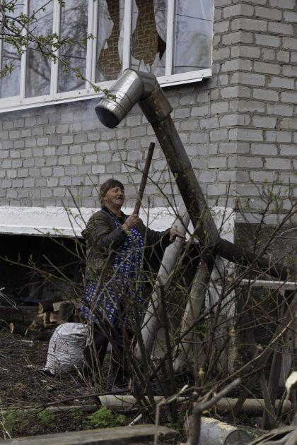 Svetlana - Spartak - Repubblica Popolare di Donetsk (Ex Ucraina - Donbass). Svetlana cerca di sistemare il tubo della piccola stufetta del seminterrato.