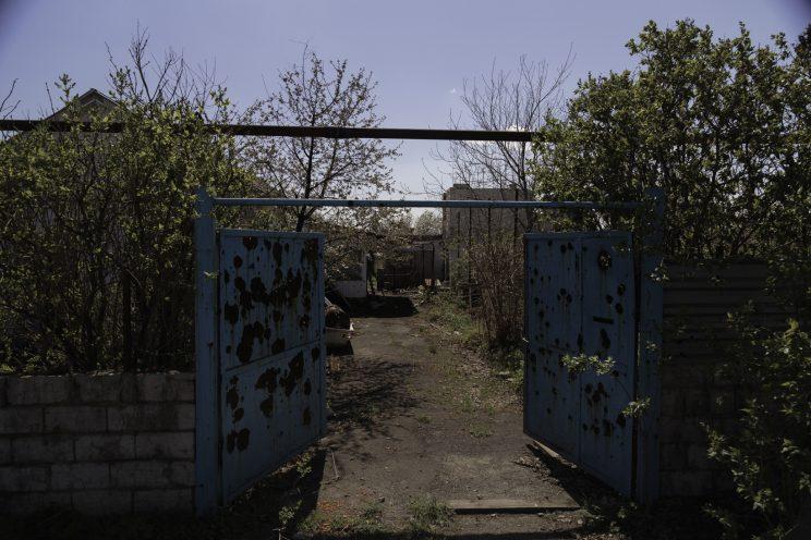 Kominternove - Repubblica popolare di Donetsk (Ex Ucraina - Donbass) - 2018. Il cancello di una casa completamente bucato dai proiettili.