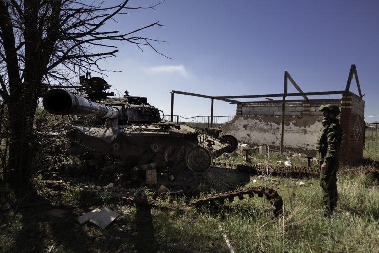 Kominternove - Repubblica popolare di Donetsk - Un soldato DPR osserva un carroarmato Ucraino distrutto.