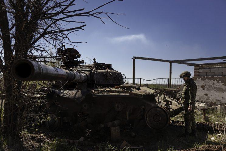 Kominternove - Repubblica popolare di Donetsk - Un soldato DPR osserva un carroarmato Ucraino distrutto..